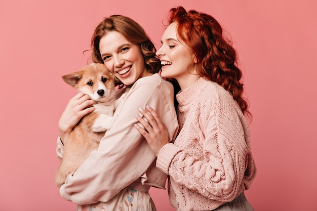분홍색 배경에 고립 된 귀여운 강아지를 들고 멋진 여자. 애완 동물과 함께 포즈를 취하는 웃는 유럽 숙녀의 스튜디오 샷. 무료 사진