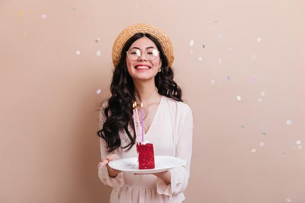 Meravigliosa donna giapponese con i capelli ricci tenendo la torta. vista frontale della donna cinese in bicchieri per celebrare il compleanno. Foto Gratuite