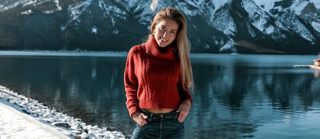 深い湖と素晴らしい山の景色の雪に覆われた海岸に屋外に立っている素晴らしい女性。特大のセーターとジーンズの陽気な女の子。化粧なしと長いブロンドの髪型。青い澄んだ空。 無料写真