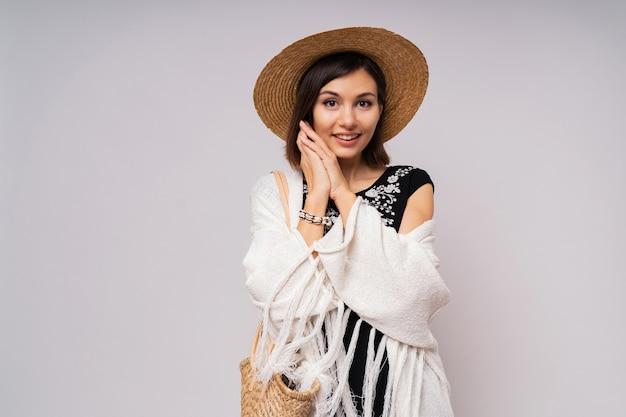 Замечательная коротковолосая женщина в соломенной шляпе и летнем бохо закрывает позирование Бесплатные Фотографии