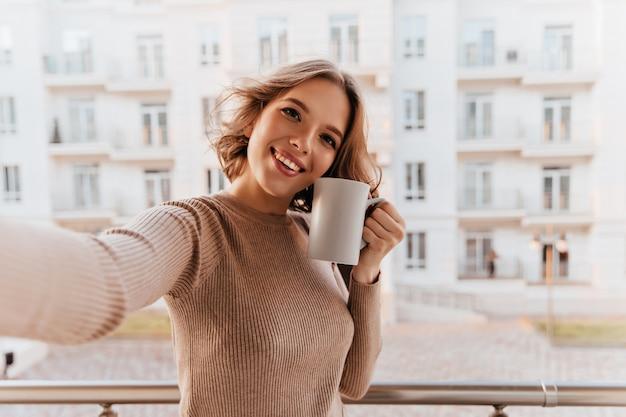 Meravigliosa donna sorridente con una tazza di caffè in piedi sulla città. ragazza bruna positiva che gode della mattina con il tè. Foto Gratuite