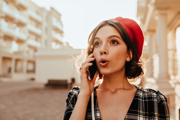 Meravigliosa ragazza sorpresa in red hat parlando al telefono. magnifica signora castana con lo smartphone in posa nella soleggiata giornata autunnale. Foto Gratuite