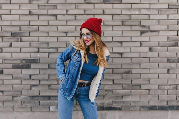 Замечательная белая дама в красной шляпе счастливые танцы на улице. наружное фото довольно белокурой девушки в джинсовой одежде весело на кирпичной стене. Бесплатные Фотографии