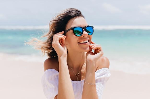 Замечательная женщина в белом наряде и блестящих очках позирует с счастливым выражением лица в жаркий летний день. приятная кавказская женщина, стоящая возле океана на небе Бесплатные Фотографии