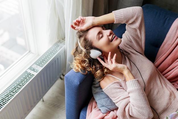 巻き毛の短い髪の素敵な女性がお気に入りの音楽を聴き、目を閉じて喜んで横になっています。かわいいピンクの部屋着。 無料写真