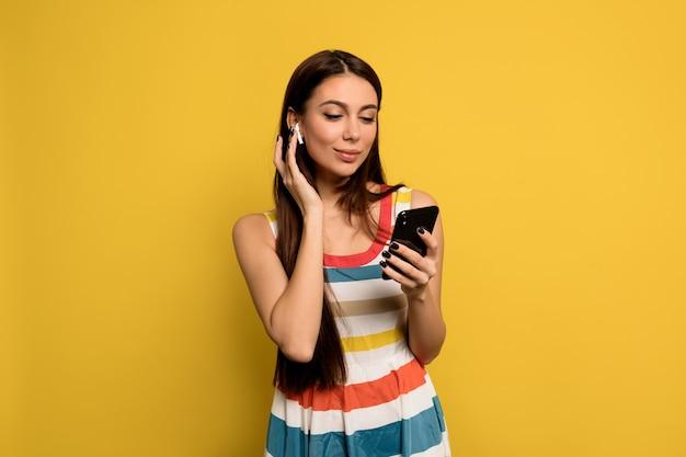 Замечательная женщина с длинными волосами и обнаженным макияжем в ярком платье слушает музыку и держит смартфон Бесплатные Фотографии