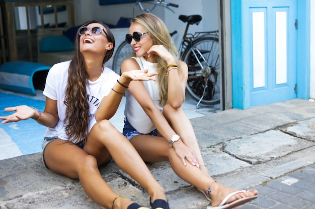 야외 입구 근처에 앉아 웃고 멋진 어린 소녀. 금발 머리와 갈색 머리는 휴가에 친구입니다. 여름 더운 날씨. 흰색 티셔츠와 청바지 반바지를 입고 있습니다. 얼굴에 선글라스 무료 사진