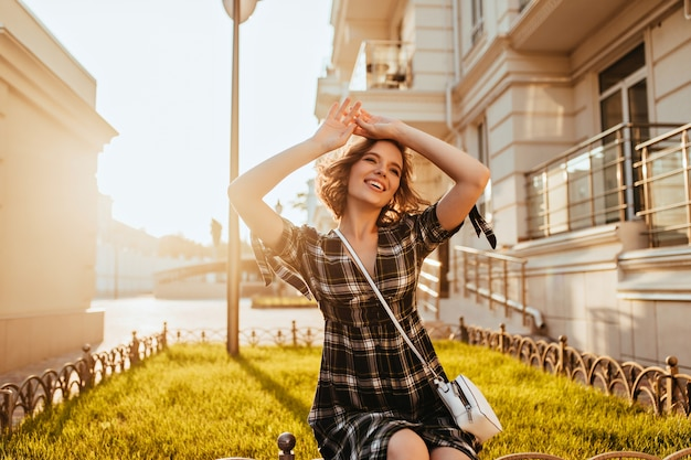 Wonderful young woman with little tattoo posing in sunny autumn day. laughing fashionable white lady relaxing in september morning. Free Photo