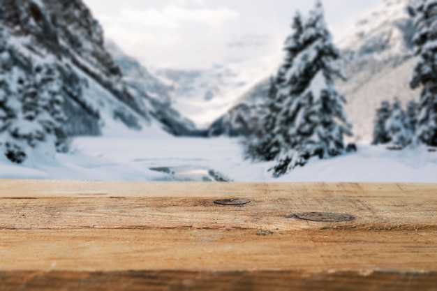 Wood board and mountains with trees in snow Free Photo