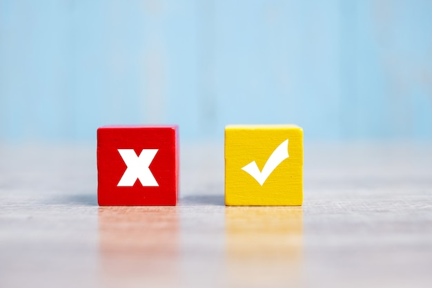 Wood cubes block with wrong and right symbol on table Premium Photo
