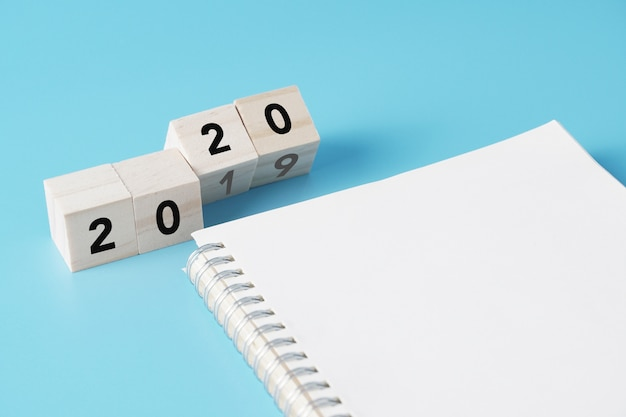 Wood cubes changing from new year 2019 to 2020 concept with blank notebook for to do list Premium Photo