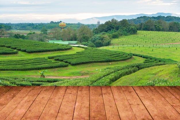 Wood floor perspective view with tea plantation farm and view of mountain and hot air balloon in background. Premium Photo