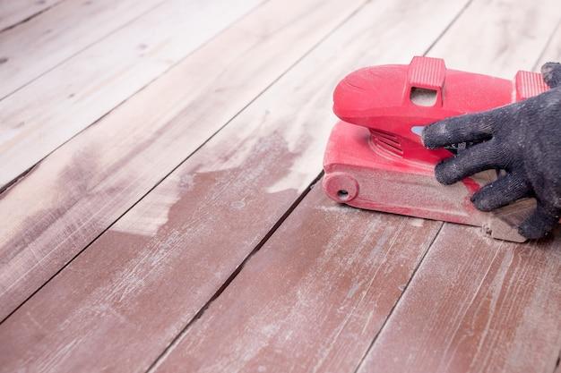 Wood floor polishing maintenance work by grinding machine. Premium Photo
