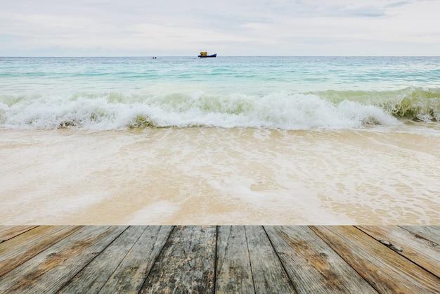Wood floor on waves crashing on the beach Photo | Premium Download