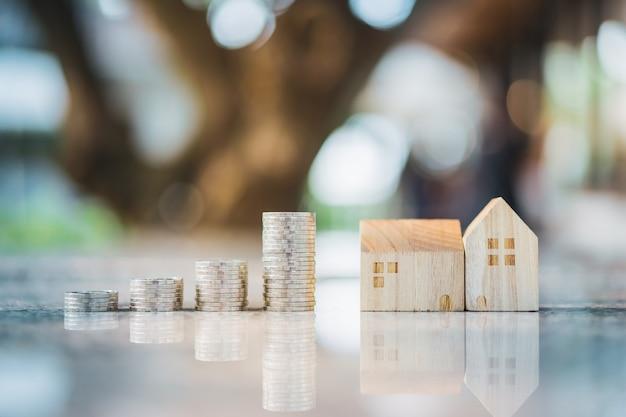 Модель деревянного дома и ряд монетных денег на белом фоне, рынок недвижимости, торговая недвижимость, ипотечные концепции Premium Фотографии