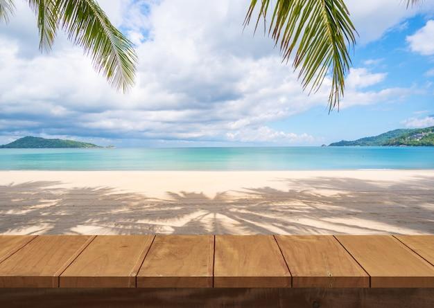 木製のテーブルとビーチの海砂と夏の日のヤシ Premium写真