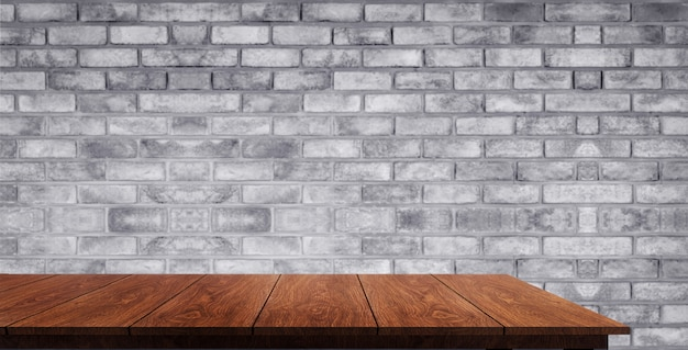 Wood table in front of brick wall blur background. Premium Photo