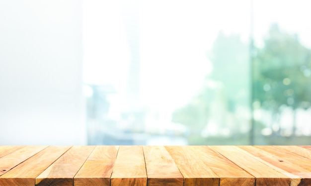 Wood table top on blur window glass,wall background with city view.for montage product display or design key visual layout Premium Photo