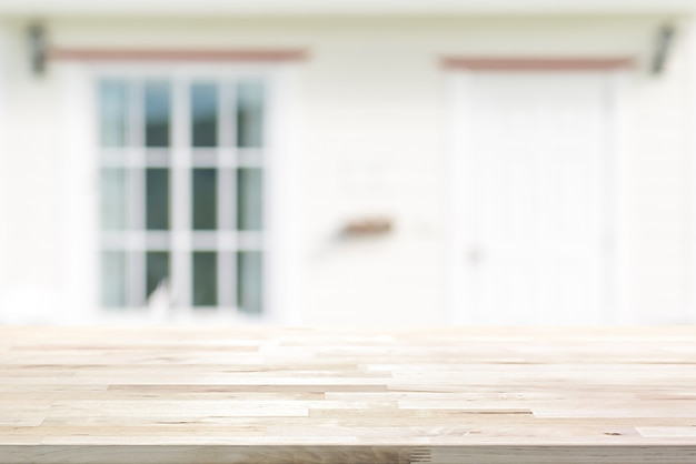 Wood table top on blurred white house front with door and glass window Premium Photo