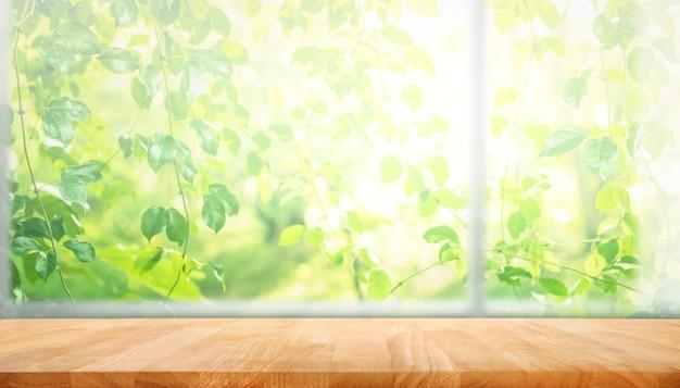 아침에 정원 꽃 배경으로 창의 흐림에 나무 테이블 탑 프리미엄 사진