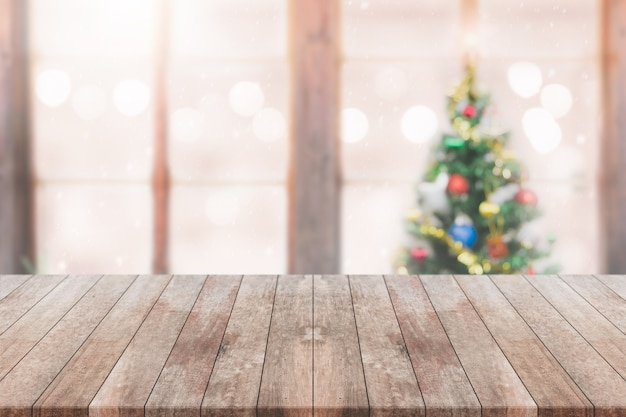Wood Table Top On Blur With Bokeh Christmas Tree Background With Snowfall    Can Be Used