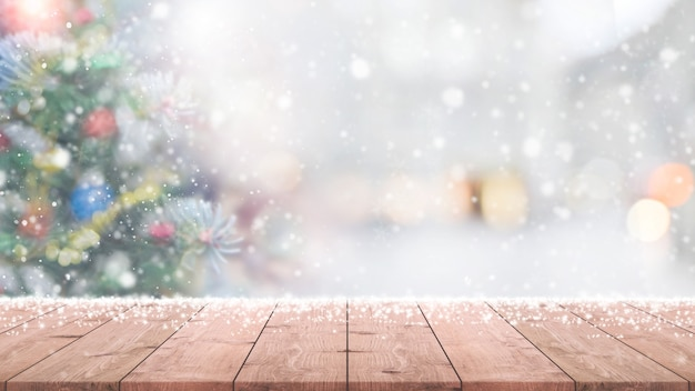 Wood table top on blur with bokeh christmas tree background with snowfall Premium Photo