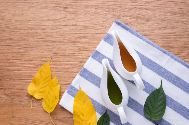 Wood table with cup of juice and leaf. top view. Premium Photo