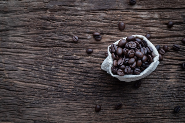 Wood table with fresh coffee bean in cloth sack. Premium Photo