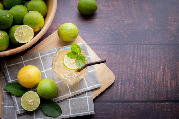 Wood table with freshly squeezed lemon juice with mint and sliced lemon. Premium Photo