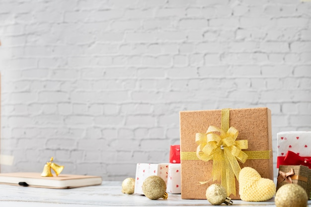 Wood table with gift box and yellow heart on white brick wall texture background, view from above board. Premium Photo