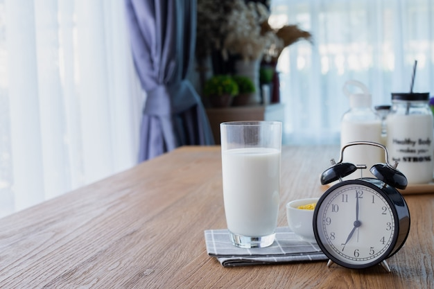 Wood table with glass of milk and retro alarm clock in living room. Premium Photo
