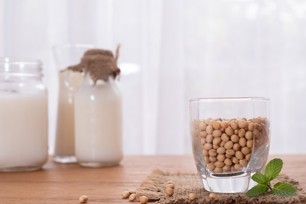 Wood table with soybean and milk. Premium Photo