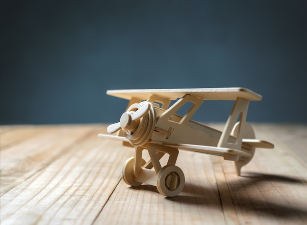 Wood toy airplane on wood table view from above. Premium Photo