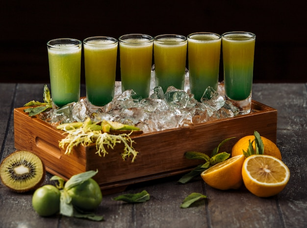 Wood tray of kiwi and orange shotes served in ice cubes Free Photo