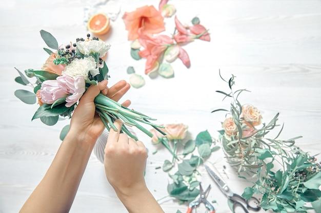 Изображение подрезанное взглядом женского флориста аранжируя букет с инструментами пользы цветков на белой предпосылке woodem. доставка цветов. копировать пространство рабочее место и профессиональная концепция Premium Фотографии