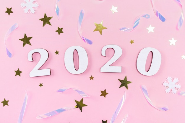 Wooden 2020 numbers and christmas decorations, confetti, stars and snowflakes Premium Photo