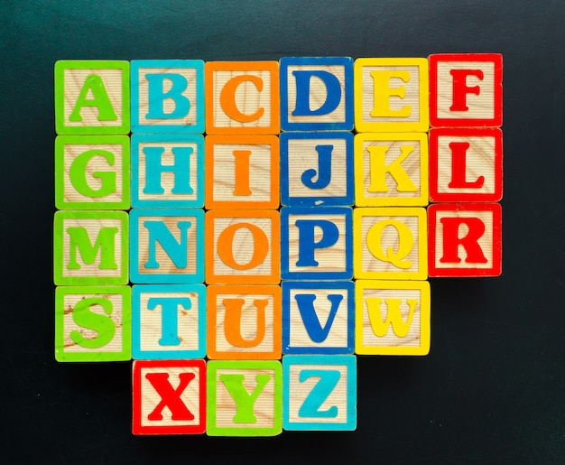 Wooden alphabet blocks with letters on wooden board Premium Photo