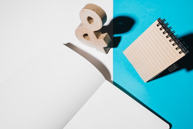 Wooden ampersand sign; spiral notepad and blank white page on dual wallpaper Free Photo