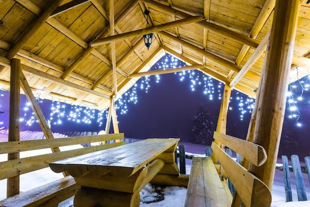 크리스마스 조명과 나무 아버는 눈 덮인 전나무 나무의 표면에 대해 저녁 안개가 자욱한 겨울철에 스키 슬로프에 선다 프리미엄 사진