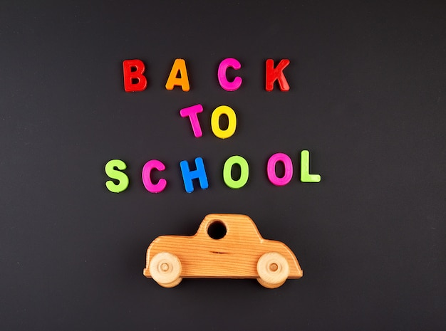 Wooden baby car on black chalk board, concept back to school Premium Photo