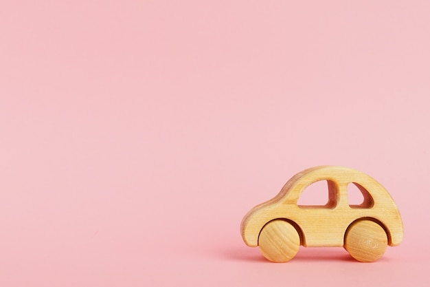 Wooden baby car on a pink pastel background with copyspace. Premium Photo