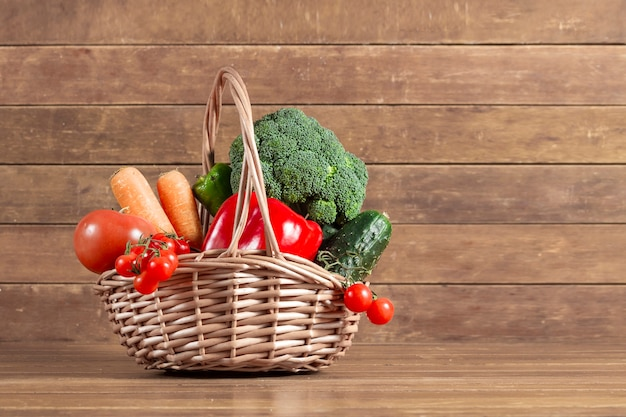 Wooden background with basket full of vegetables Free Photo