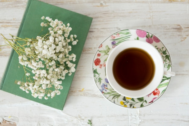 Wooden background with cup of tea, flowers and book Free Photo