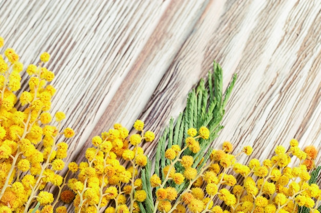 Wooden background with floral border. twigs of blooming mimosa lie on wood table. flowery background. Premium Photo