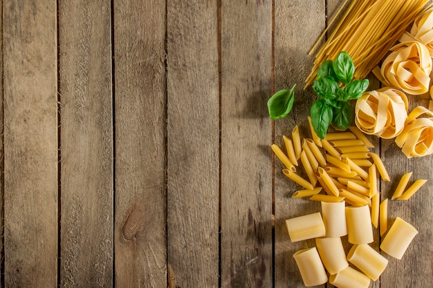 Wooden Background With Italian Pasta And Basil Photo