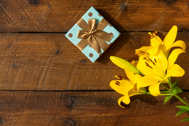 Wooden background with lilies and cute gift Free Photo