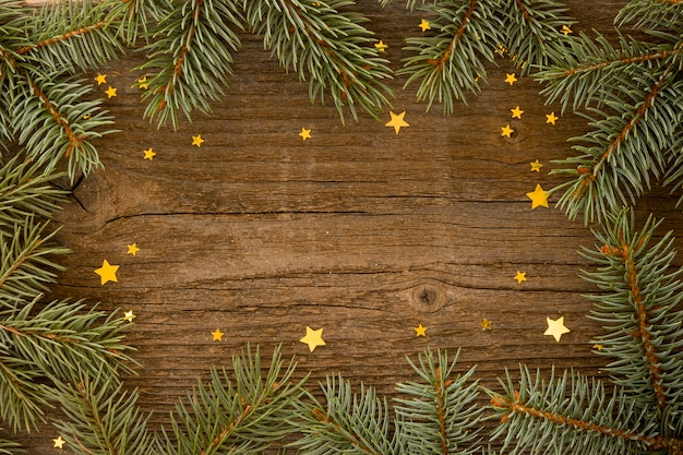 Wooden background with pine leaves and stars Free Photo