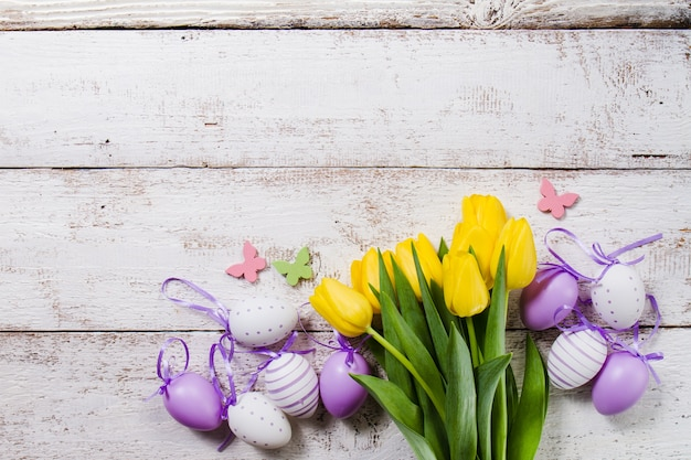 Wooden background with yellow tulips and easter eggs Free Photo