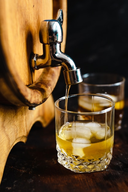 Wooden barrel and glasses of whiskey. Premium Photo