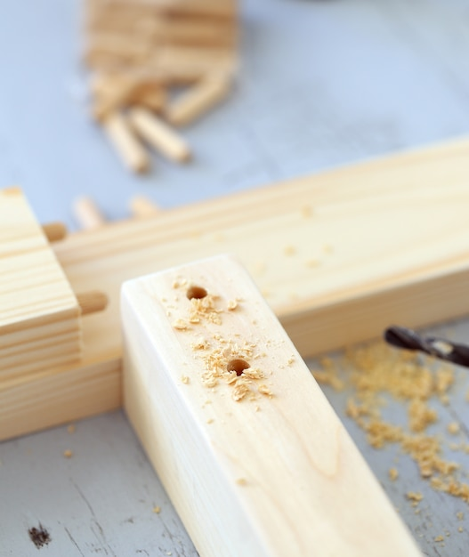 Wooden bars being drilled Free Photo